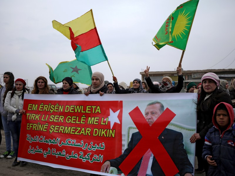 People hold flags and carry a banner reading 'We condemn and denounce the attacks of the Turkish government against our people in Afrin' during a protest against Turkish attacks on Afrin, in Hasaka, Syria, on January 18, 2018. Photo: Reuters / Rodi Said