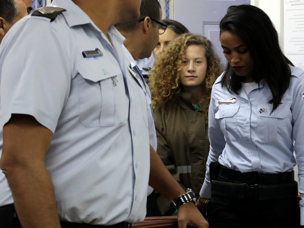 Palestinian teen Ahed Tamimi enters a military courtroom escorted by Israeli Prison Service personnel at Ofer Prison near the West Bank city of Ramallah on December 28, 2017. Photo: Reuters / Ammar Awad