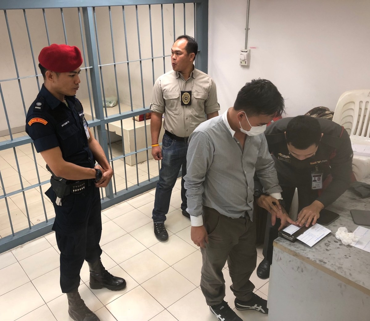 Thai police take the finger prints of Boonchai Bach. Photo: AsiaWorks
