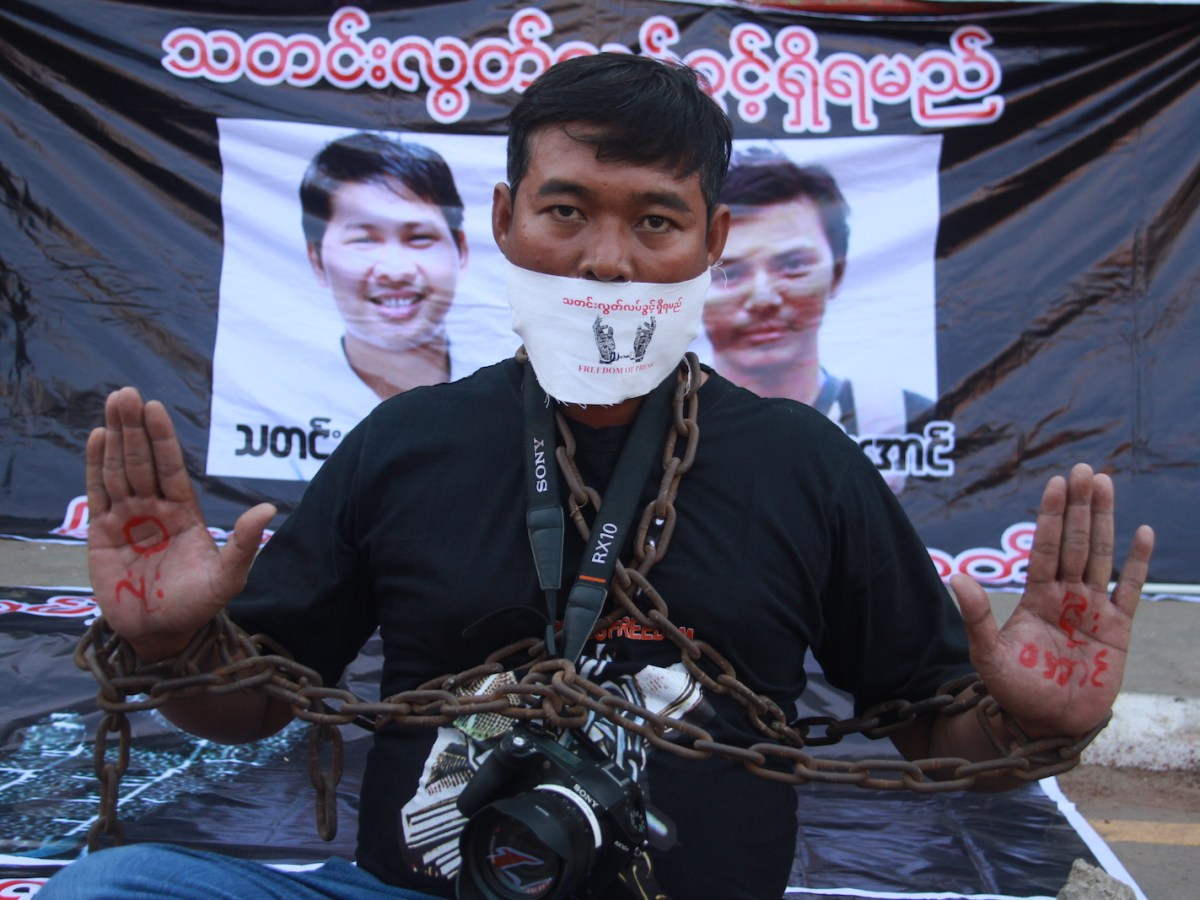 A journalist poses during a protest by local media to demand the release of Reuters journalists Wa Lone and Kyaw Soe Oo (pictured in posters behind) in Pyay on December 27, 2017. Photo: AFP/Thiha Lwin