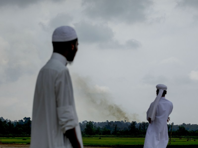 Rohingya men look at smoke billowing above what is believed to be a burning village in Myanmar's Rakhine state, as members of the Muslim minority group take shelter in a no-man's land between Bangladesh and Myanmar, in Ukhia on September 4, 2017. Photo: AFP/ K M Asad