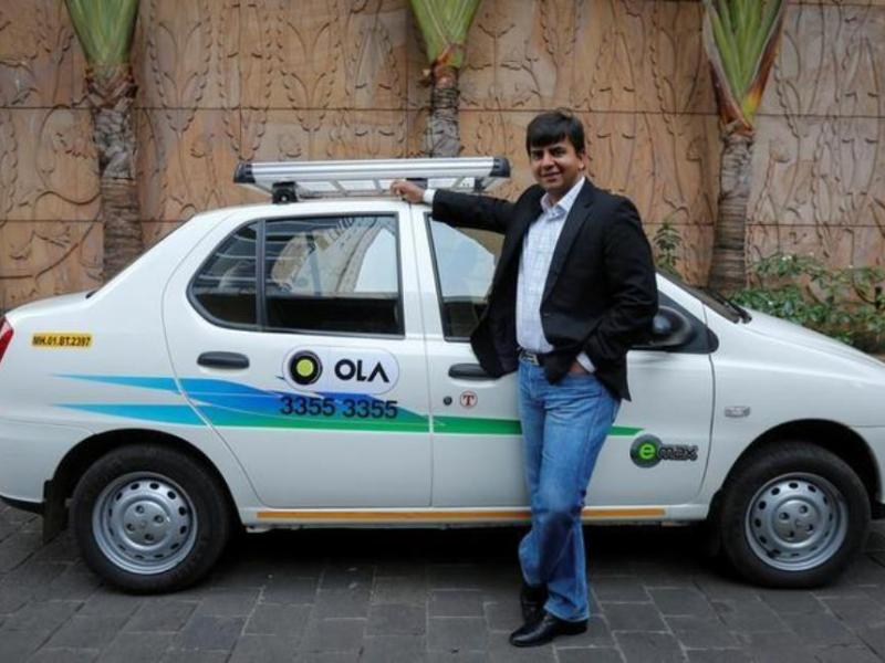 Bhavish Aggarwal, CEO and co-founder of Ola, an app-based cab service provider, poses in front of an Ola cab in Mumbai. Photo: Reuters