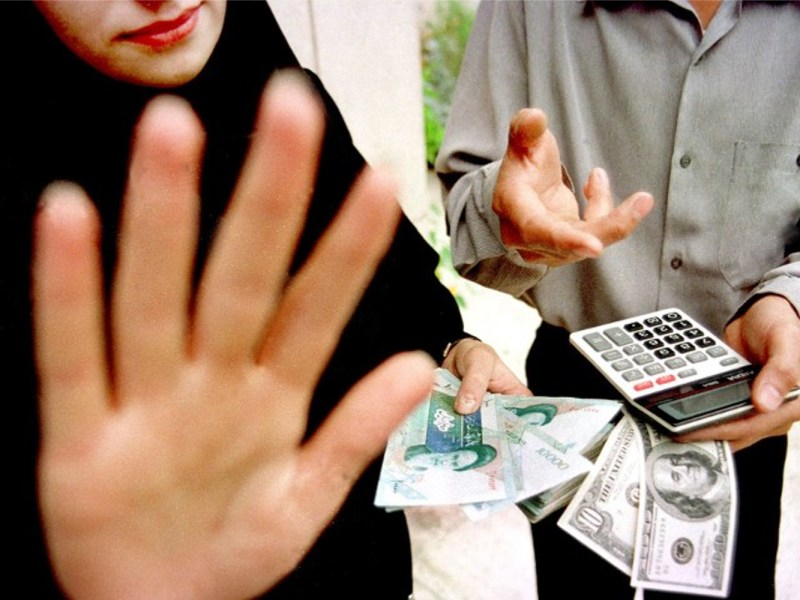 An Iranian woman changes Iranian rial for dollars from a street exchange dealer in Tehran. Photo: AFP/Behrouz Mehri