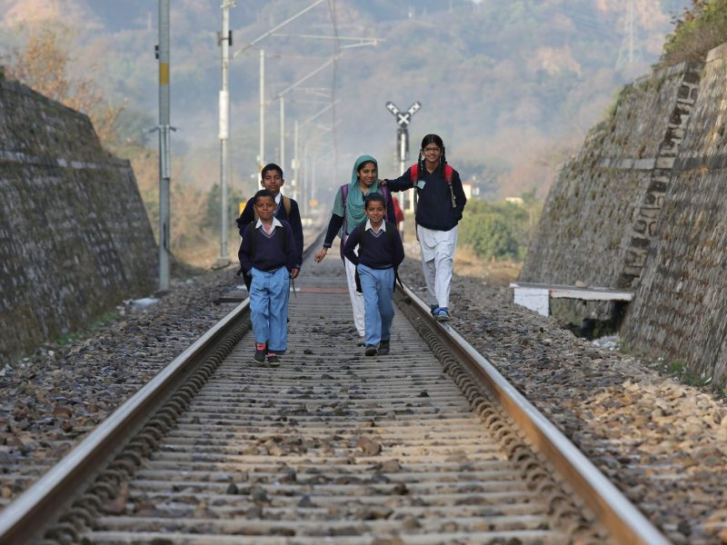 Schoolchildren walk on a railway line as they approach their school on the outskirts of Jammu. Photo: Reuters