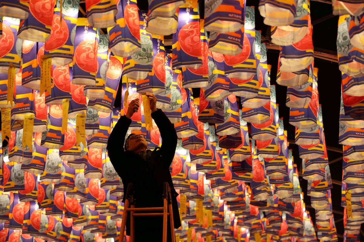 A visitor hangs his wish to a lantern at a festival ahead of Chinese New Year in Xian, Shaanxi province. Photo: Reuters / China Daily