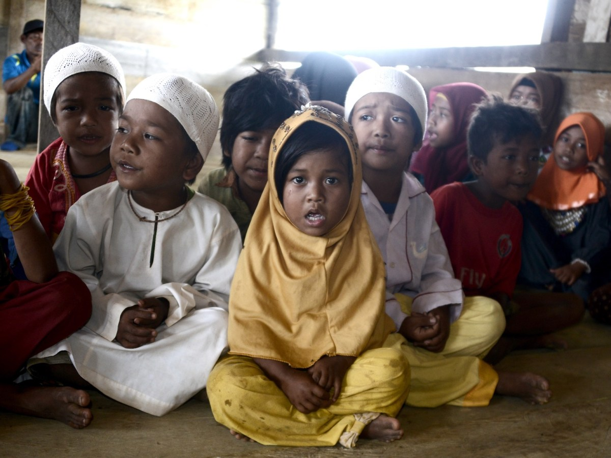"Children from the""Orang Rimba"" tribe -- whose name translates as ""jungle people"", who have been converted to Islam and given up their nomadic ways, wearing Islamic skullcaps and hijabs as they gather to recite the Koran, in the Batang Hari district of Jambi province. Photo: AFP/Goh Chai Hin"