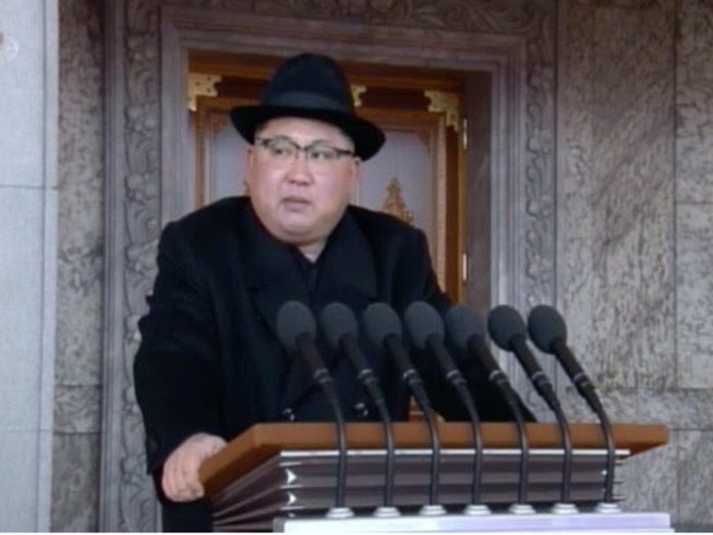 A still from an official North Korean video of Kim Jong-un shows the leader giving a speech while firmly grasping the lectern with the facial expression of an unwell person.