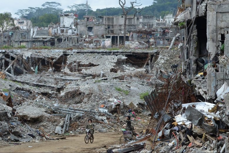 A soldier rides a bicycle past bombed-out buildings in what was the main battle area in Marawi on the southern island of Mindanao on October 25, 2017, days after the military declared the fighting against IS-inspired Muslim militants over. Philippine troops of a southern Philippine city where Islamic State supporters waged a brutal five-month battle began leaving Marawi on October 25, as a group of journalists were given the first ever press tour of the devastated city. / AFP PHOTO / TED ALJIBE