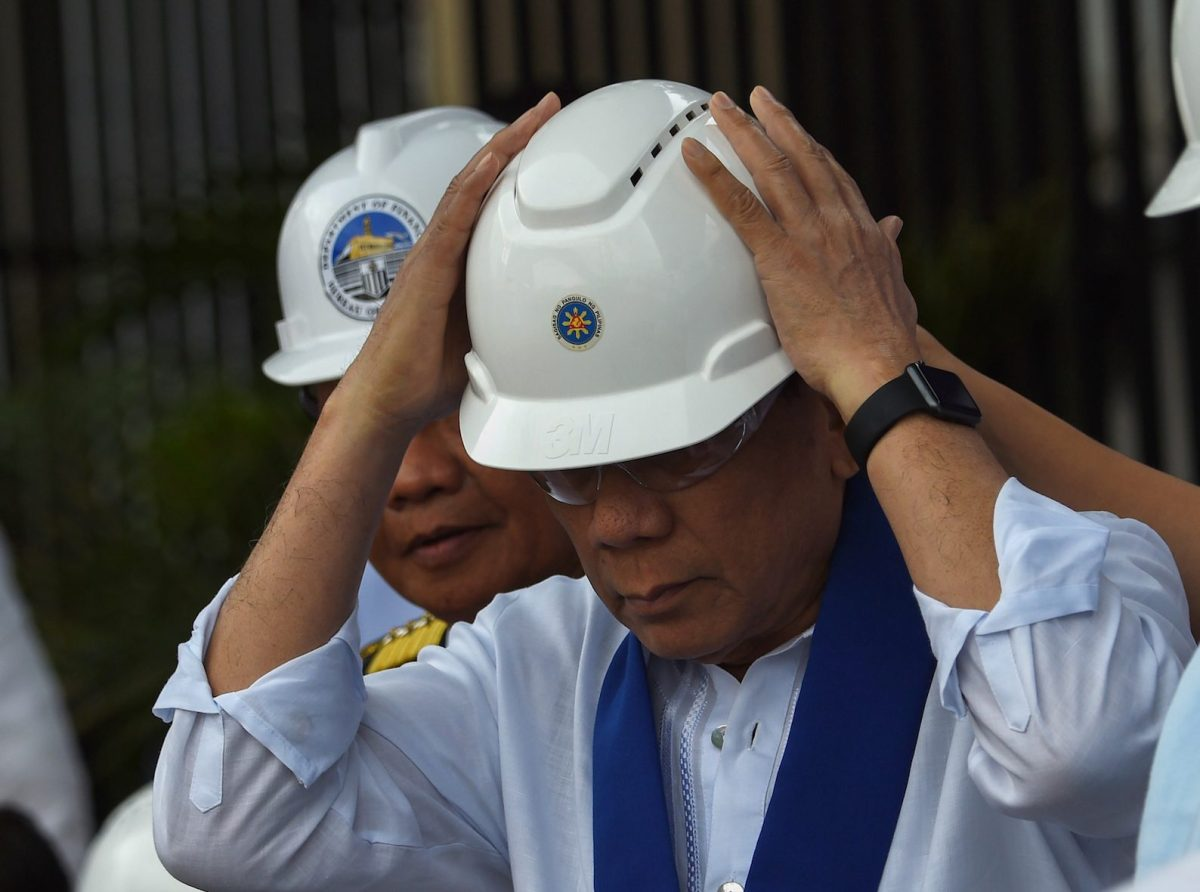 Philippine President Rodrigo Duterte wears a hardhat at the country's customs bureau. Photo: AFP/Ted Aljibe