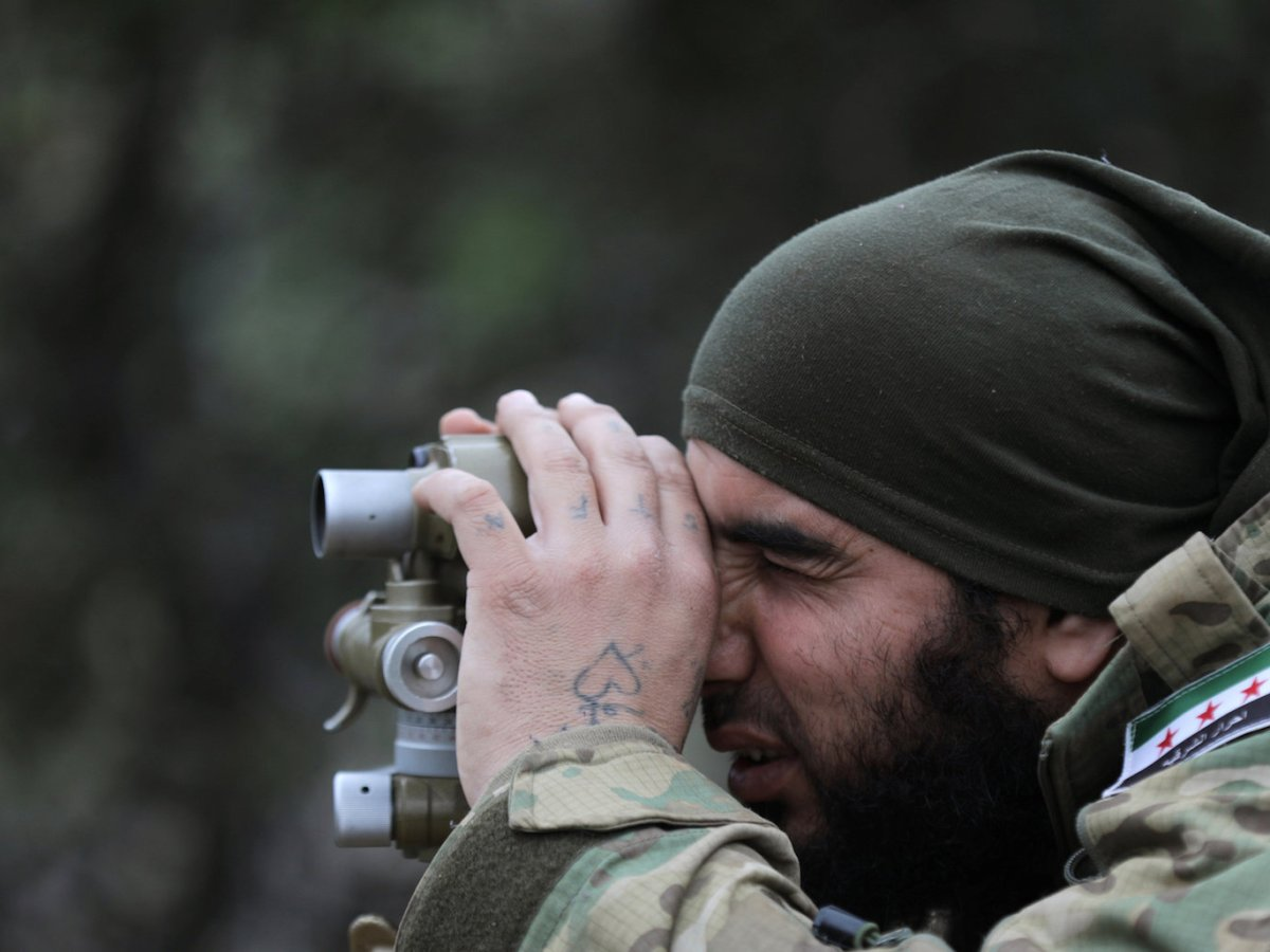 A Turkish-backed Free Syrian Army fighter looks through a pair of binoculars outside of Afrin, Syria, on February 17, 2018. Photo: Reuters / Khalil Ashawi