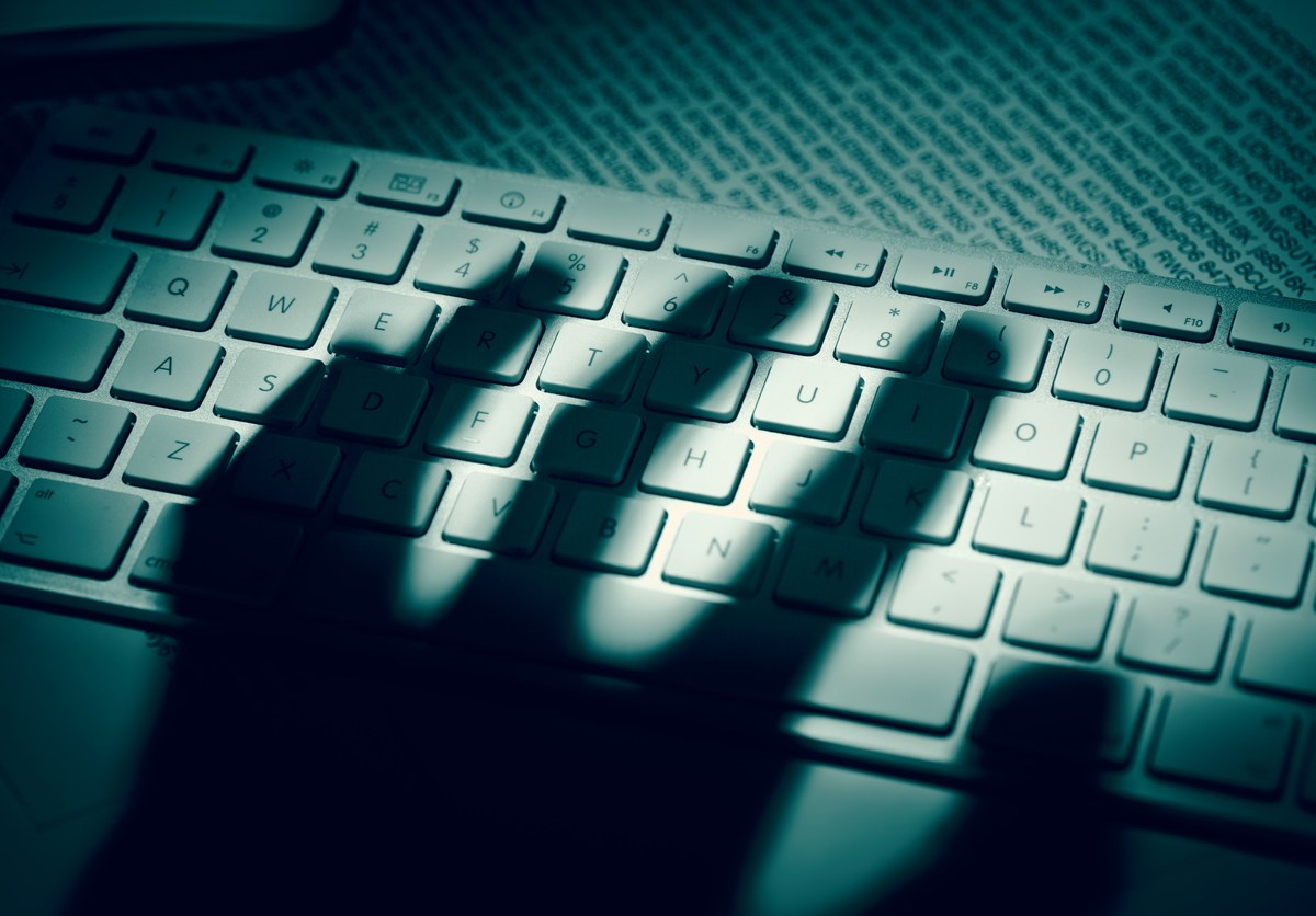A menacing hand's shadow on a computer keyboard in front of printed computer data. Image: iStock/Getty Images