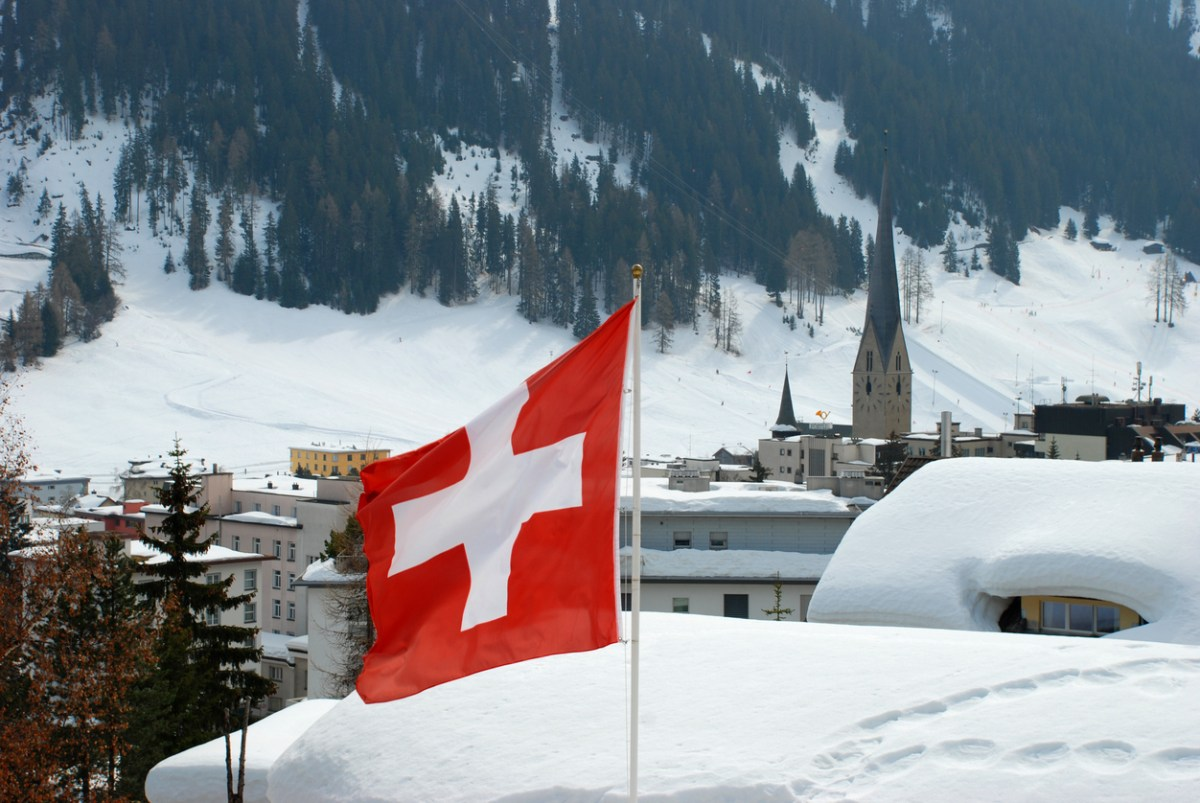 Swiss flag in Davos town with church and mountains in the background. Davos is a ski resort and location of the annual World Economic Forum. Photo: iStock