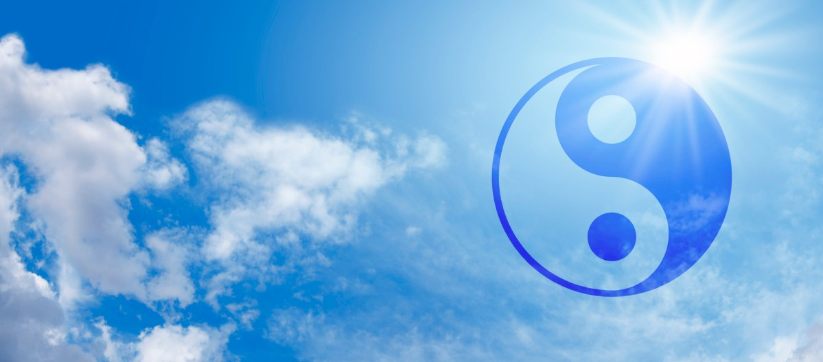 Wide blue sky panorama with fluffy clouds and a bright sunburst behind a semi-transparent blue Yin Yang Symbol. Photo: iStock