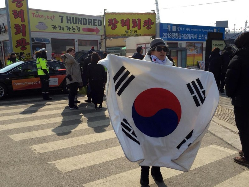 A solitary anti-North Korea protestor shouts her pro-South Korea, pro-Trump slogans while draped in a South Korean flag. Photo: Andrew Salmon/Asia Times