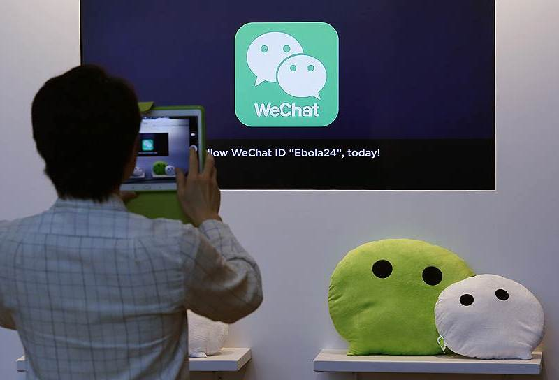 A man takes a picture of the WeChat logo. The social networking app that 900 million Chinese use is now hitting roadblocks in its overseas forays. Photo: Xinhua