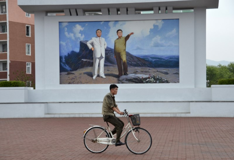 A local resident cycles past a mural depicting former North Korean leaders Kim Il Sung and Kim Jong Il in the North Korean port of Rajin, July 18, 2014. Photo: Reuters / Yuri Maltsev