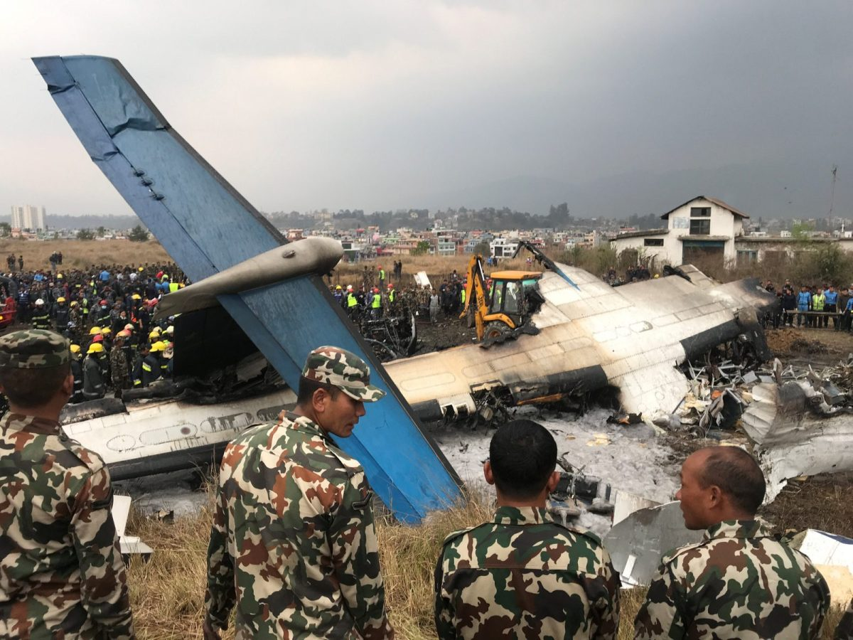 The US Bangla plane after the crash with rescue workers scouring the wreckage at Kathmandu airport. Photo: Reuters/Navesh Chitrakar