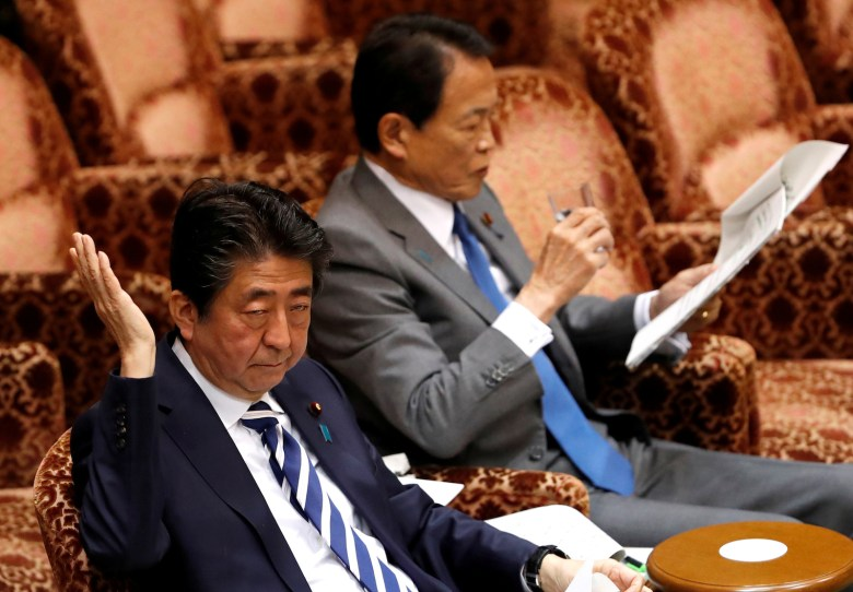 Japanese PM Shinzo Abe and Finance Minister Taro Aso attend at an upper house session in parliament in Tokyo on March 19.  Photo: Reuters/Issei Kato