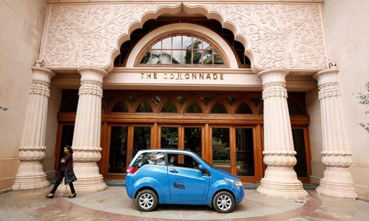 A woman walks past a Mahindra e2o electric car during a media preview in Bangalore. Photo: Reuters / Abhishek Chinnappa