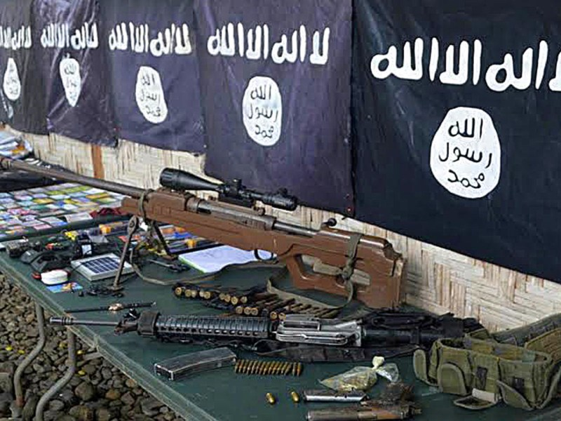 In this photo taken on November 26, 2015, weapons and ISIS flags recovered from members of a criminal gang who pledged allegiance to ISIS are displayed in Palimbang town, Sultan Kudarat province, on the southern island of Mindanao. Eight members of a criminal gang that pledged allegiance to Islamic State jihadists were killed in a firefight with the military in the southern Philippines, officials said November 27.  AFP PHOTO / STR / AFP PHOTO / STR