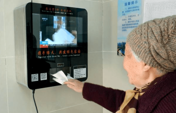 A senior resident scans her face for toilet paper at a public restroom in Nanjing. Photo: Xinhua via CFP