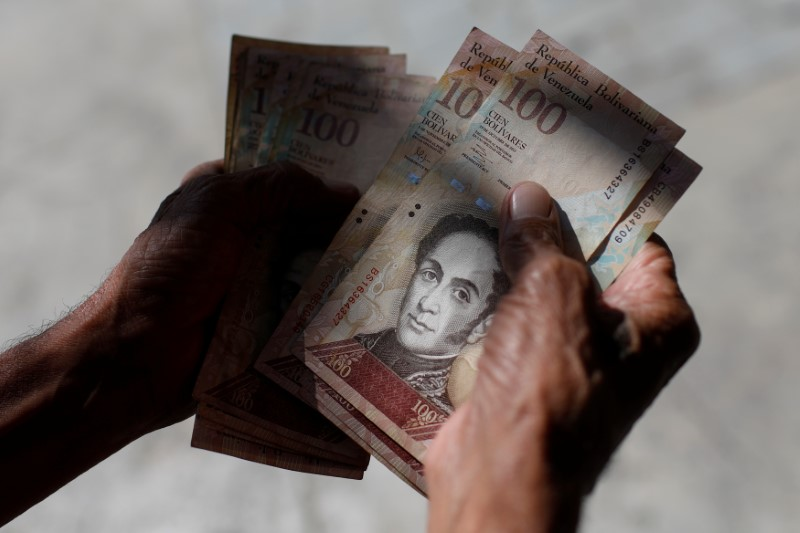 A man counts Venezuelan bolivar notes in downtown Caracas in January. Photo: Reuters/Marco Bello