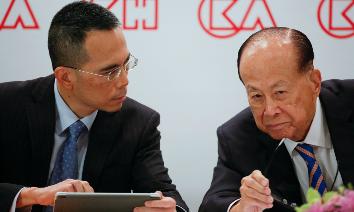 Li Ka-shing (right) listens to his son Victor Li, Co-Managing Director and Deputy Chairman of CK Hutchison Limited, during a news conference in Hong Kong, China, on March 16, 2018. Photo: Reuters/Bobby Yip