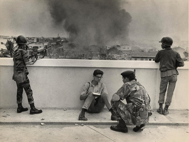 Vietnam War reporter Dan Southerland takes notes with conflict raging in the background in Saigon, May 1968. Photo: UPI/Bill Snead (used with permission)