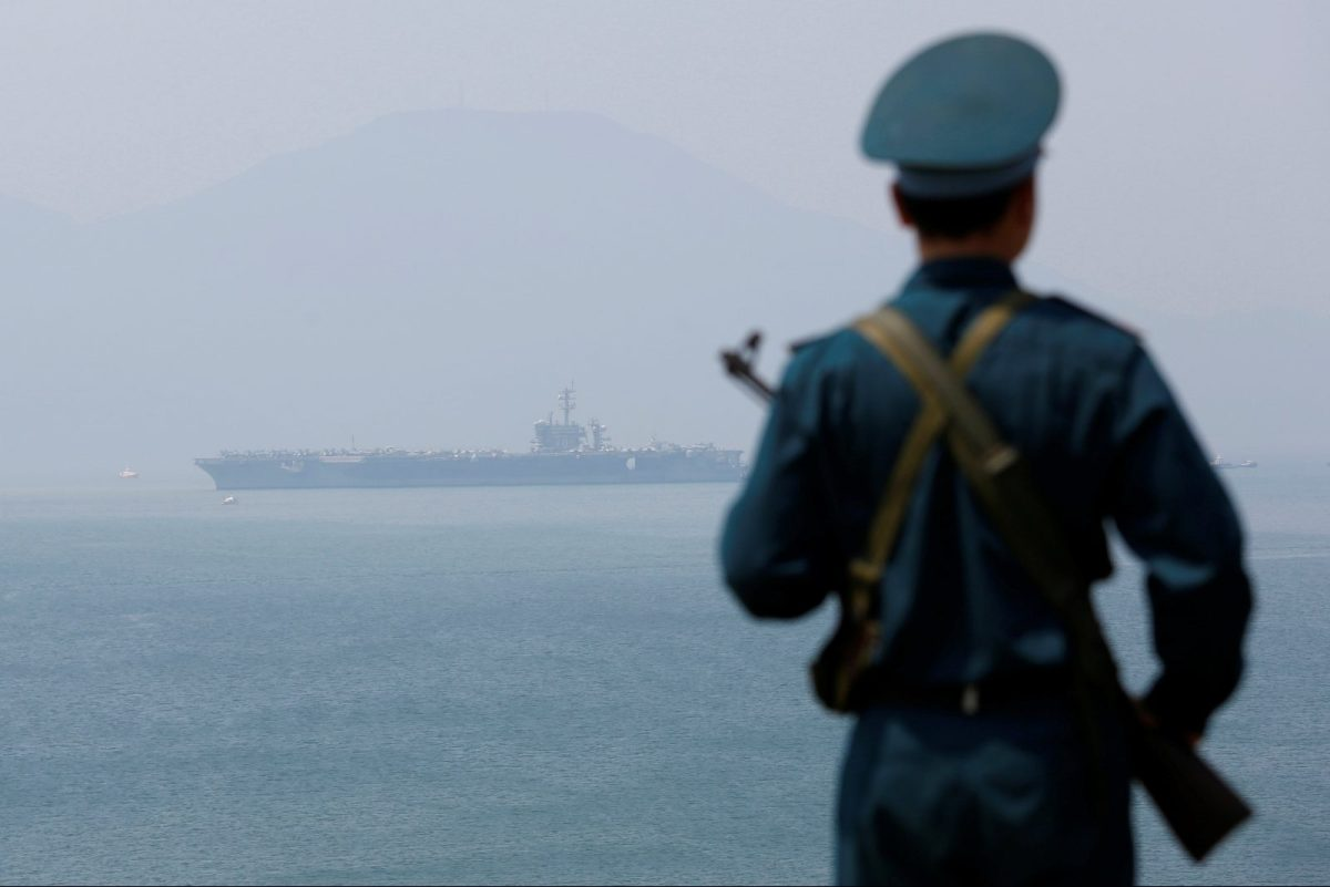 A Vietnamese soldier keeps watch in front of US aircraft carrier USS Carl Vinson after its arrival at a port in Danang, Vietnam March 5, 2018. Photo: Reuters/Kham