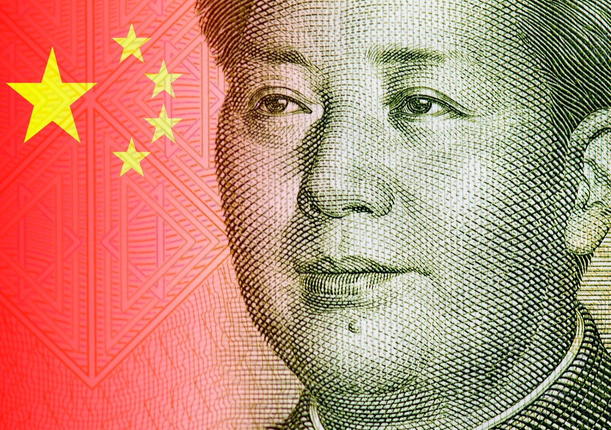 Close-up portrait of Mao Zedong, portrait of the chairman Mao and detail of Chinese flag. Image: iStock