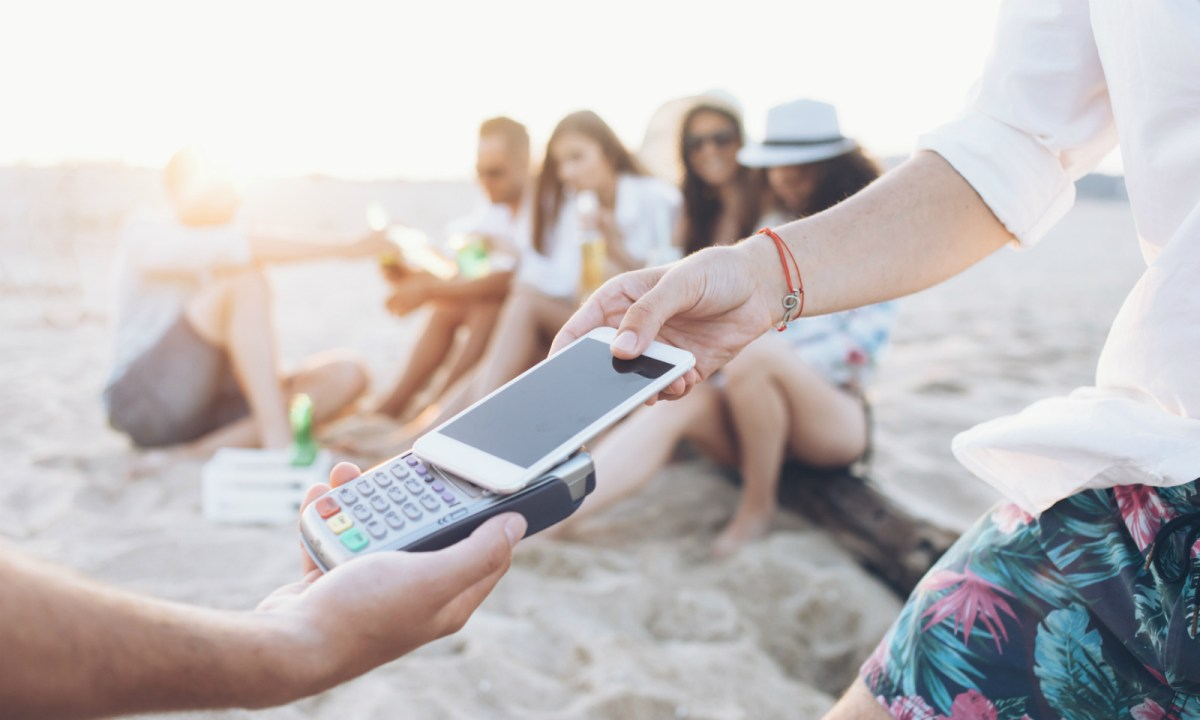 A man using a smart phone to pay for goods on a beach. Photo: iStock