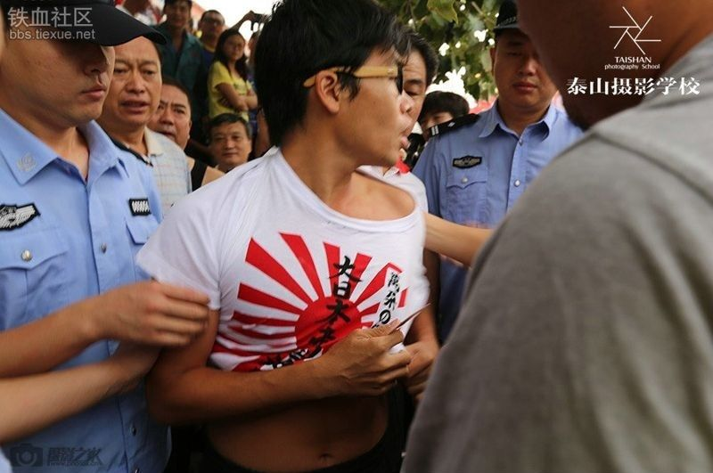 A Chinese youth, wearing a T-shirt bearing the war flag of the Imperial Japanese Army, is seen in a scrum of police and onlookers. Photo: People's Daily via tiexue.net