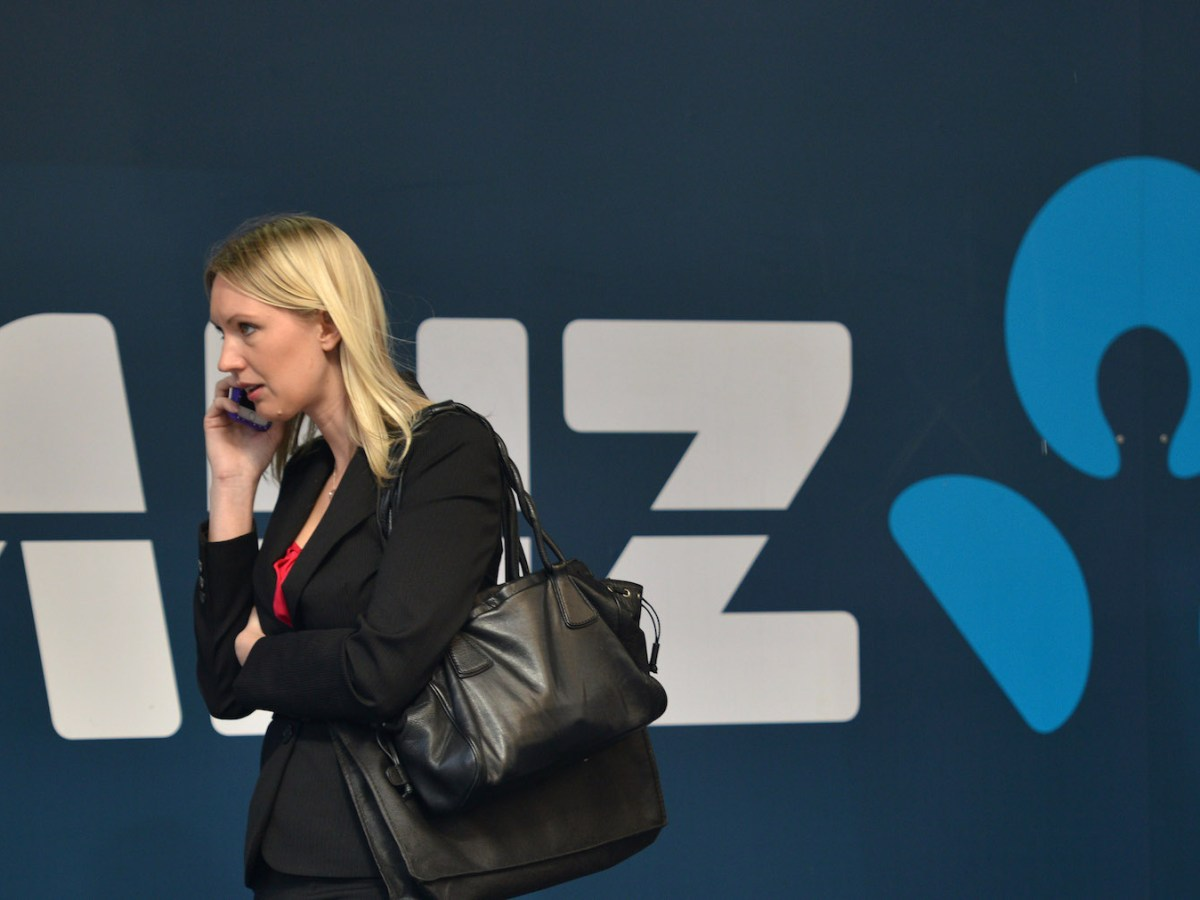 A woman walks in front of an ANZ bank sign in the central business district of Sydney on August 12, 2014. Photo: AFP/Peter Parks