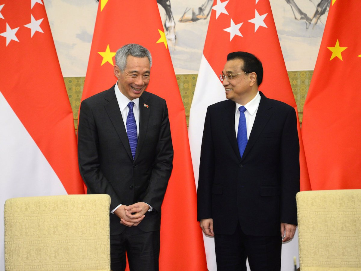 Chinese Premier Li Keqiang laughs with Singapore's Prime Minister Lee Hsien Loong during a signing ceremony at the Diaoyutai State Guesthouse in Beijing, April 8, 2018. Picture: Parker Song/Pool via Reuters