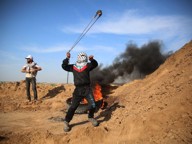 Demonstrators throw rocks with slingshots and burn tires at the border with Israel on April 11. PHOTO: AFP/Hassan Jedi/Anadolu Agency