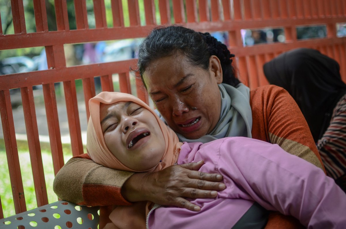 Relatives of a man who died after consuming tainted homemade alcohol cry outside of a hospital in Cicalengka, Bandung Regency, West Java, Indonesia on April 9. Photo:  Antara Foto/Raisan Al Farisi / via Reuters