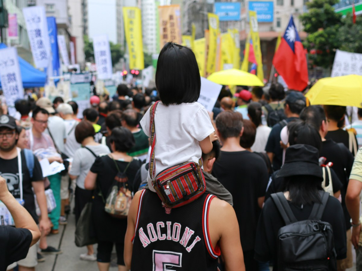 A girl rides on a protester's shoulder during the July 1 march in 2017. Photo: Asia Times