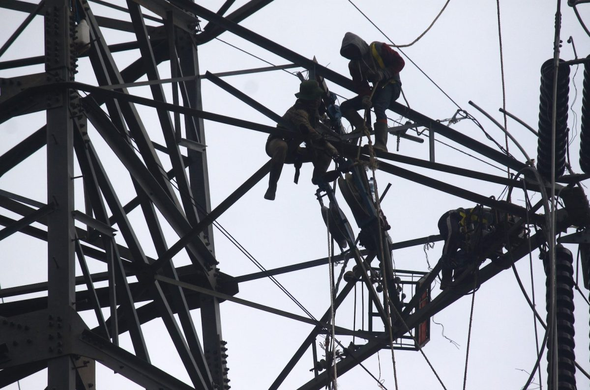 Workers assemble cables at an extra-high voltage tower in Jakarta, February 16, 2018. Photo: NurPhoto via AFP Forum/Aditya Irawan