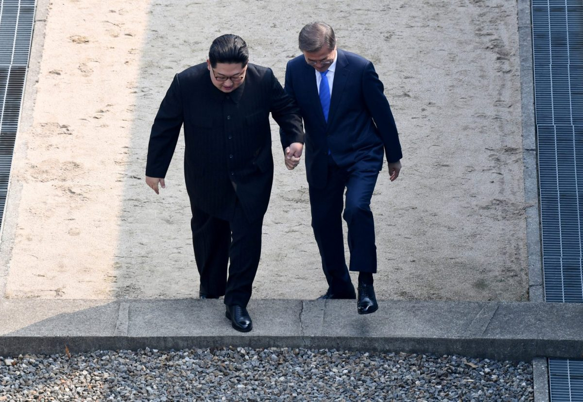 Moon Jae-in and Kim Jong-un step across the border together. Photo: Korea Summit Press Pool via Reuters