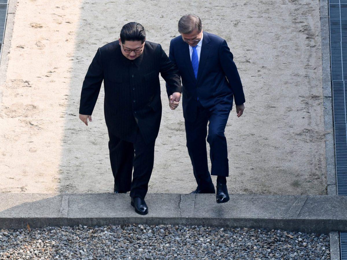 Moon Jae-in and Kim Jong-un step across the border together. Photo: Korea Summit Press Pool via Reuters