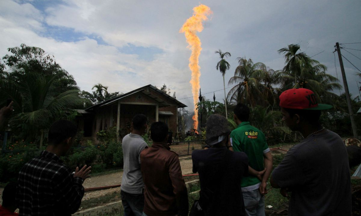 Locals watch as an illegal oil well burns in Ranto Peureulak, Aceh Province, Indonesia. Photo: Antara Foto/ Rahmad/via Reuters