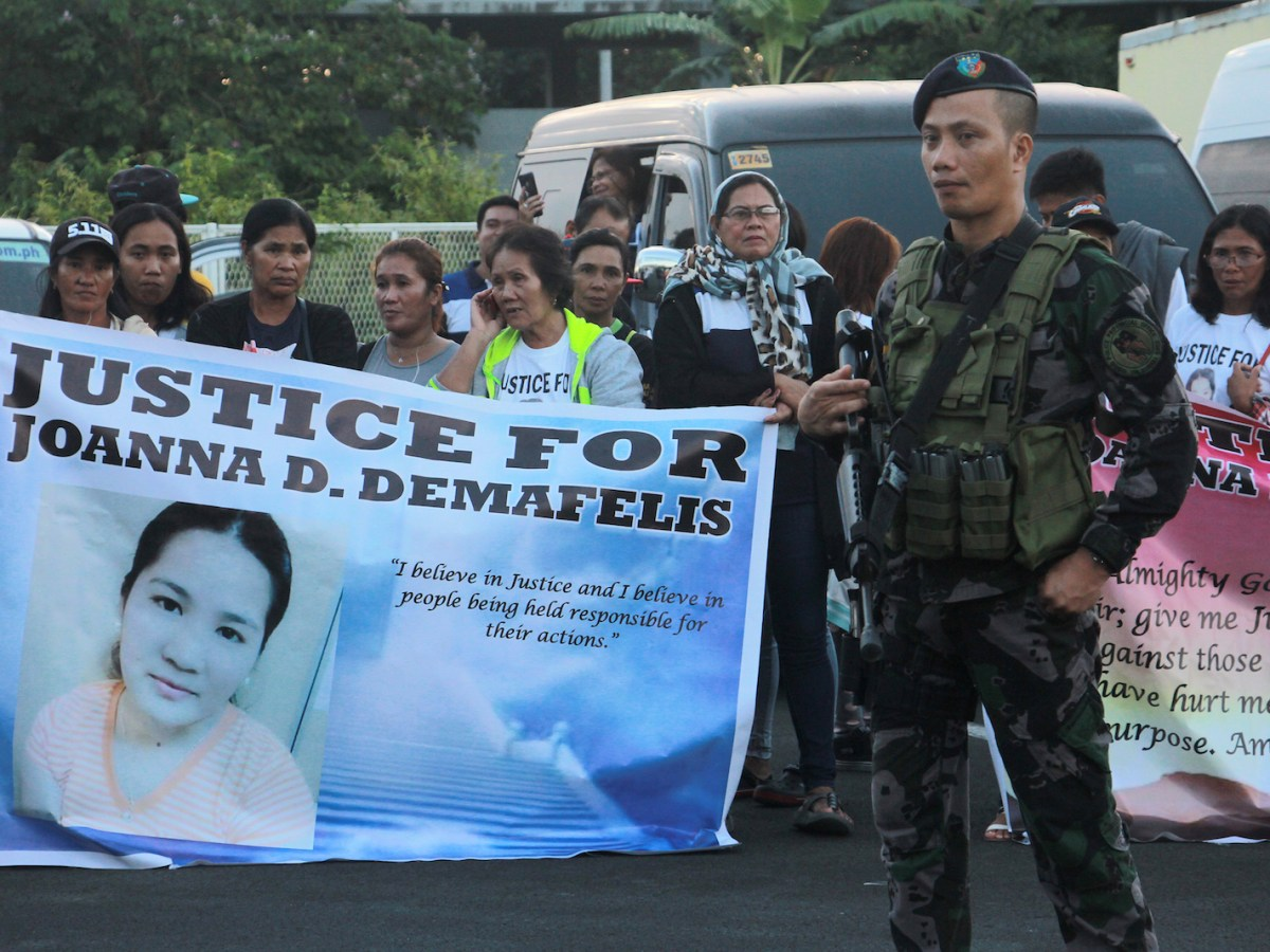 Relatives of Filipina worker Joanna Demafelis, whose body was found inside a freezer in Kuwait, hold banners as they wait for the arrival of Joanna's body from Manila at Iloilo International Airport in Iloilo province, central Philippines, on February 17, 2018. Photo: AFP