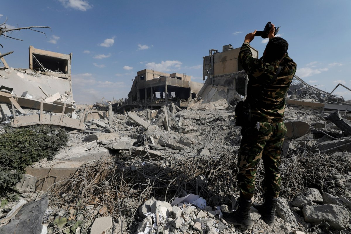 A Syrian military officer records a video inside the destroyed Scientific Research Centre in Damascus, Syria April 14, 2018. REUTERS/Omar Sanadiki
