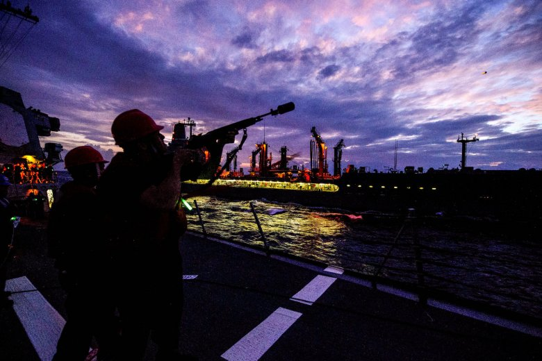 US Navy Gunner's Mate 3rd Class Shelby Wilkes of the Arleigh Burke-class guided-missile destroyer USS Mustin fires a shot line to the Military Sealift Command replenishment oiler USNS Walter S. Diehl  in the South China Sea, March 23, 2018. Picture:  US Navy/William McCann/Handout via Reuters