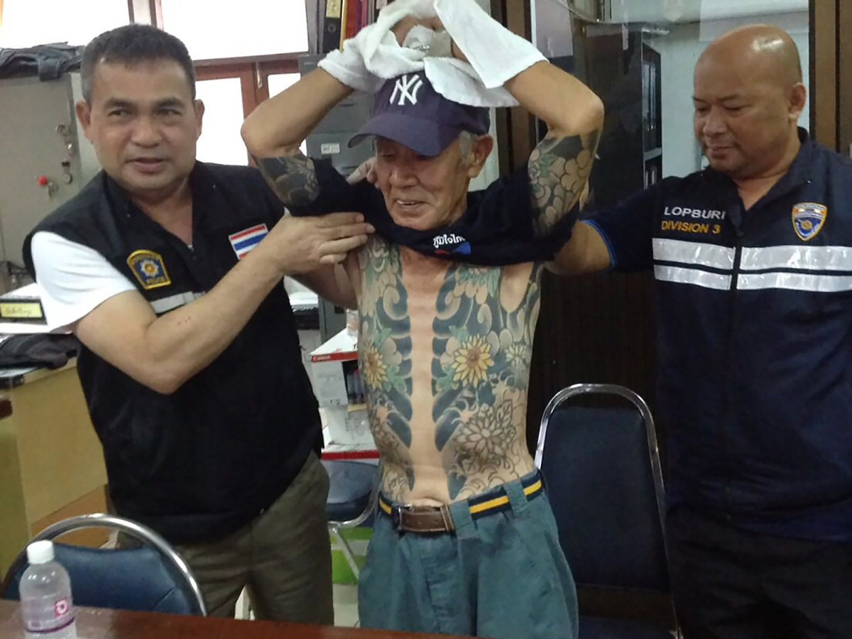 Retired Japanese crime boss Shigeharu Shirai, 72, is shown to the press in Thailand to show his gang-style tattoos at a police station after his arrest in Lopburi. Shirai had been on the run for more than 14 years. He was caught after photos of his yakuza tattoos and a missing little finger went viral on social media. Photo: AFP/ from Royal Thai Police