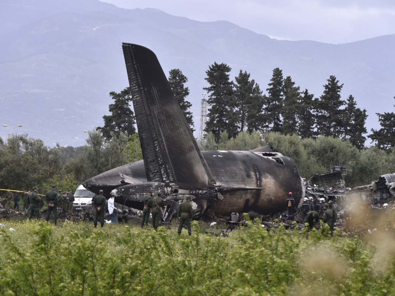 Rescuers are seen around the wreckage of an Algerian army plane. Photo: AFP / Ryad Kramdi