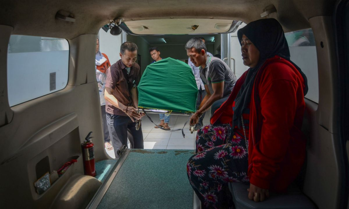The body of man who died after consuming tainted homemade alcohol is carried into an ambulance at a hospital in Cicalengka, West Java, on April 9. Photo: Antara Foto/Raisan Al Farisi/via Reuters