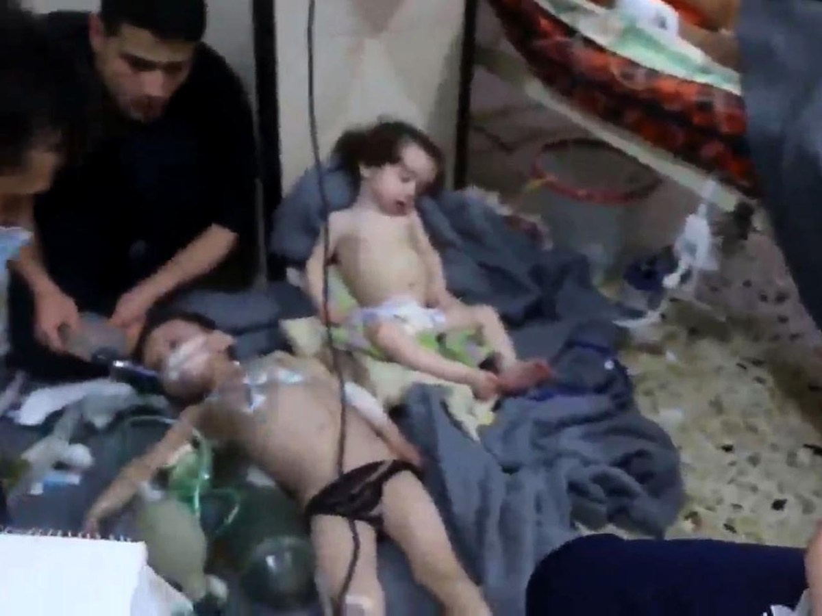 An image grab taken from a video released by the Syrian civil defence in Douma shows volunteers giving aid to children at a hospital following a reported chemical attack on the rebel-held town on April 8, 2018. Photo: AFP/Syria Civil Defence