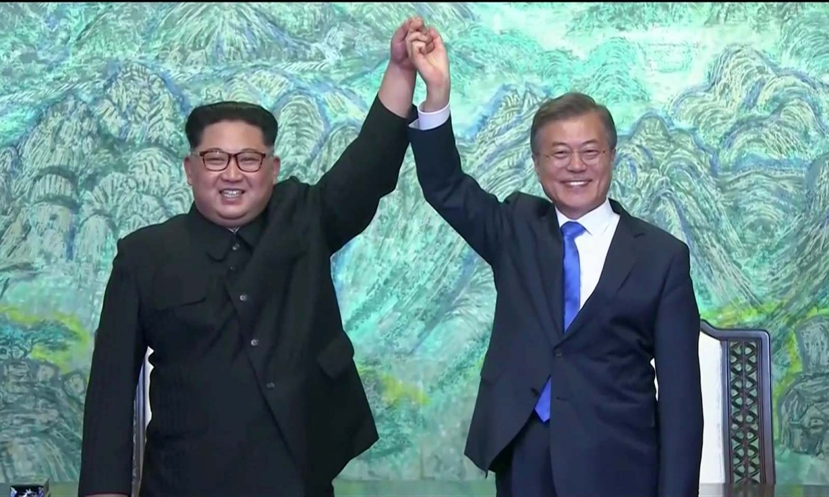 North Korean leader Kim Jong-un and South Korean President Moon Jae-in raise their hands in unity after signing agreements during the inter-Korean summit at Panmunjom on April 27, 2018. Photo: Reuters TV frame grab