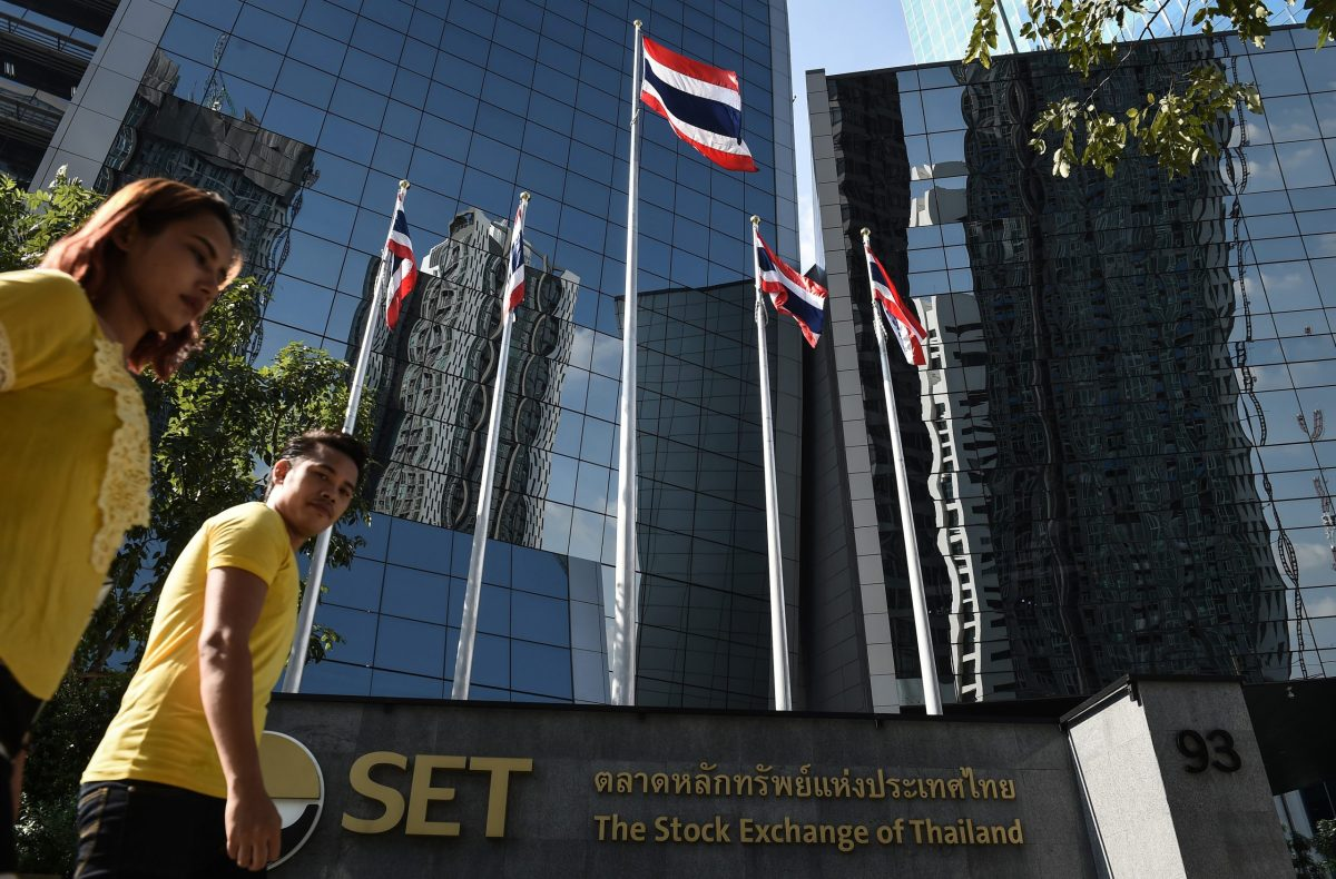 People walk past Thai flags outside of the Stock Exchange of Thailand in Bangkok. Photo: AFP